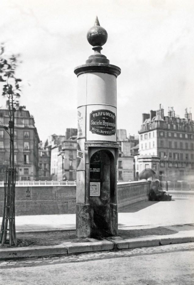 Un urinario público dentro de una columna de Rambuteau con un anuncio sobre perfume, París ca.1865